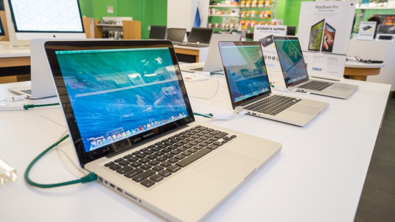 Several laptops opened on a desk.